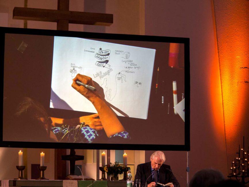 So sah das aus: Meine zeichnenden Hände un der Block auf einer großen Leinwand hinter den Vorlesenden. Foto: Regine Christansen.