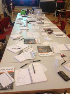Eine lange Tafel voller Papier, Hefte und Stifte. @ Ania Groß