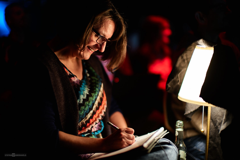 Das Bild zeigt mich, Ania Groß, von der Seite beim Zeichnen. Der Saal ist dunkel, rechts im Bild steht die kleine Leuchte, die meinem Block erhellt. Foto: © Stefan Groenveld