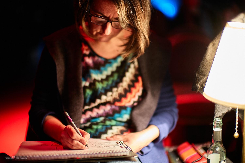 Das Bild zeigt mich, Ania Groß, vorn vorn beim Zeichnen. Der Saal ist dunkel, rechts im Bild steht die kleine Leuchte, die meinem Block erhellt. Foto: © Stefan Groenveld